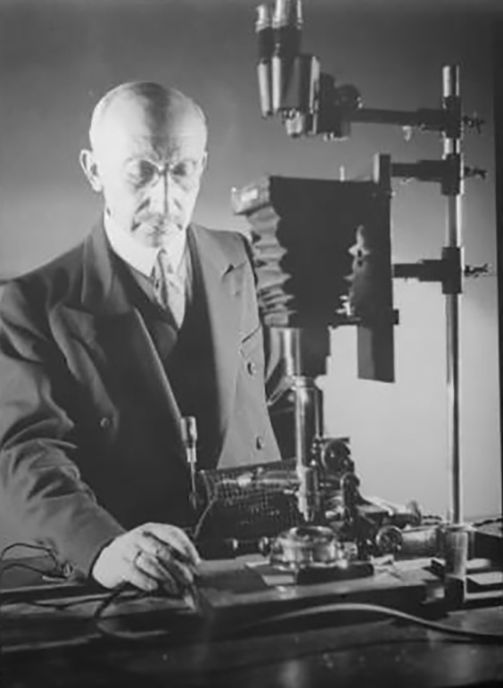 Dr. L. Bendikson with camera for microphotography. Undated. photCL 107 vol13 pg26 (140). (The Huntington Library)