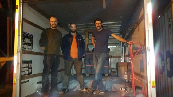 From left to right, Daniel Krull, Randall Paulhamus, and Seth Gottlieb in the back of a box truck with the wooden parts of the press.